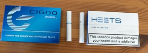 A packet of Cigoo Sticks and HEETS side-by-side